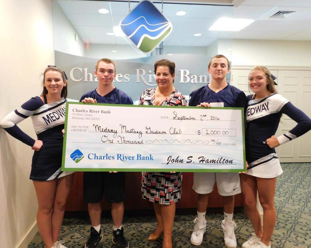 Photo Caption: (Medway) Ann Sherry, Charles River Bank Senior Vice President of Customer Care and Relationship Development, presents a donation check of $1,000 to the Medway Mustang Gridiron Club represented by cheer and football captains: Sarah O'Connor, Dylan Ehrmanntraut, Patrick Travers, and Julianne Pratt in support of the 2016 season.