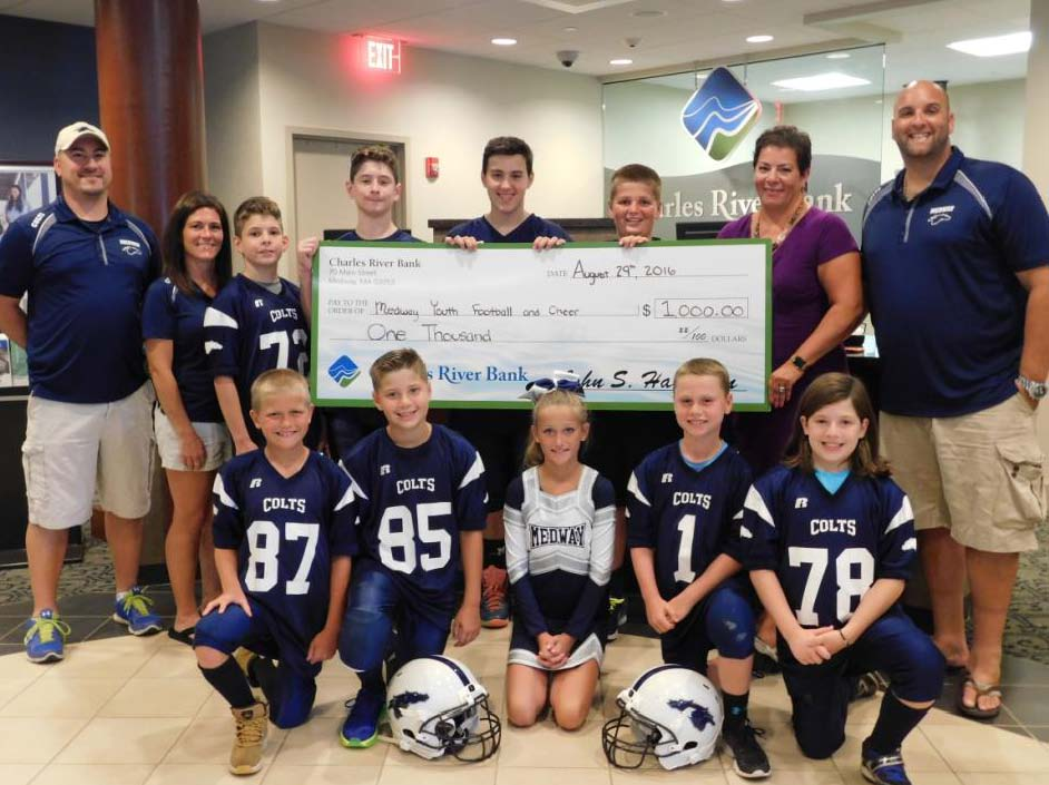 Photo Caption: (Medway) Ann Sherry, Charles River Bank Senior Vice President of Customer Care and Relationship Development, presents a donation check of $1,000 to Medway Youth Football and Cheer's President John Farrell, Treasurer Cheryl Richardson, and Vice President Matthew Applebaum, along with members of the football and cheerleading teams, to support the 2016 season.