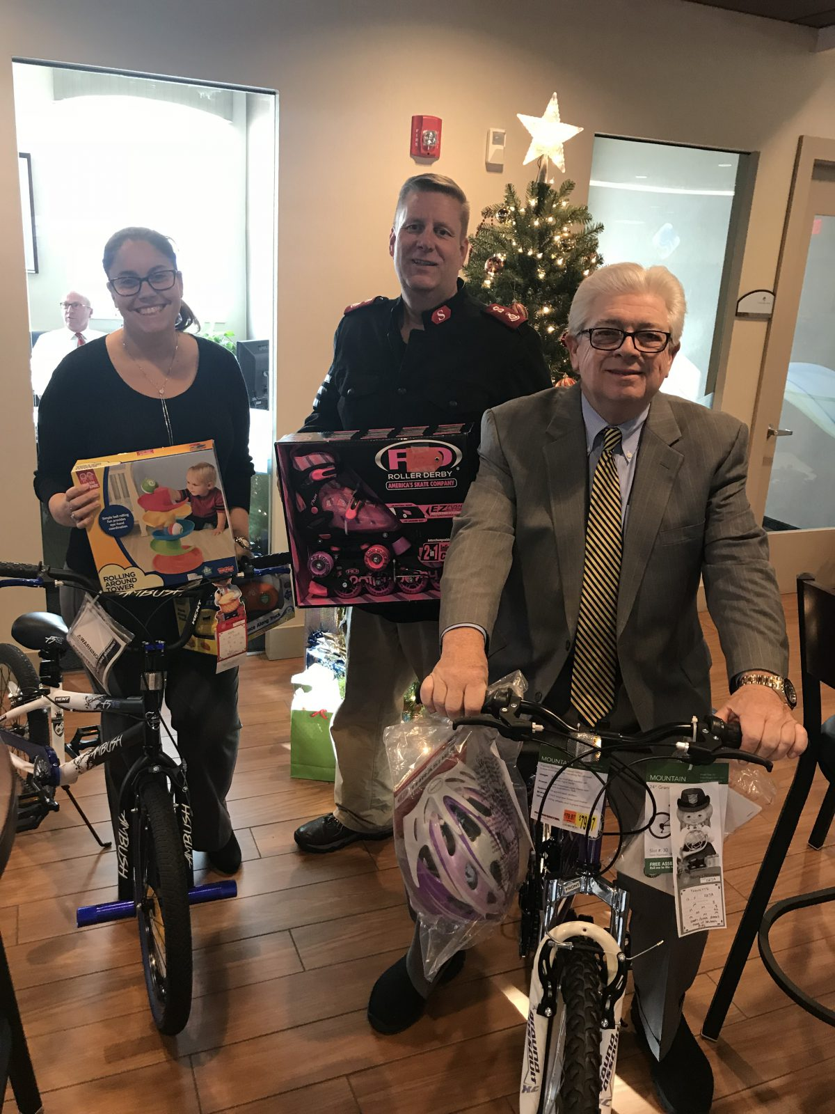Charles River Bank Marketing and Retail Banking Support Representative Catrina Lopes, Salvation Army Major Dave Irwin and Charles River Bank President and CEO Jack Hamilton display a selection of the hundreds of toys donated this year by the bank to the Salvation Army's Adopt-A-Family Program.